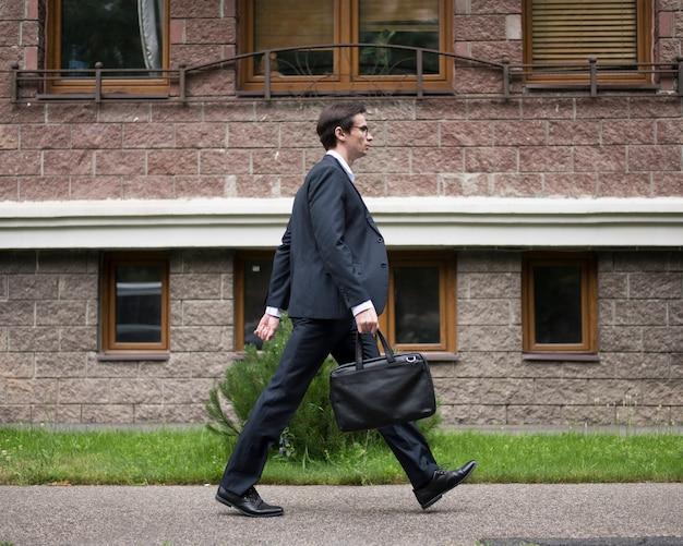 Zijaanzicht van zakenman lopen Gratis Foto