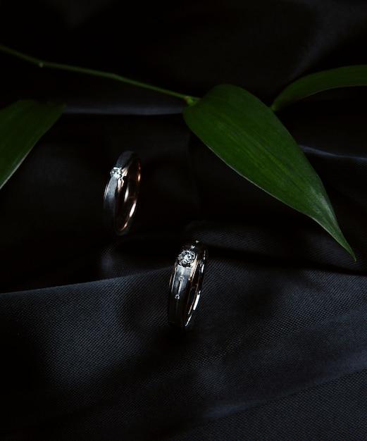 Zijaanzicht van zilveren trouwringen op zwarte muur Gratis Foto