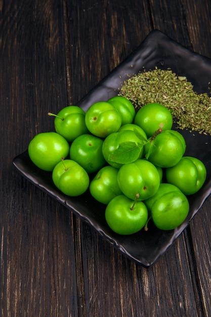 Zijaanzicht van zure groene pruimen met gedroogde pepermunt op een zwart dienblad op donkere houten tafel Gratis Foto