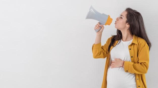 Zijaanzicht van zwangere vrouw die door megafoon spreekt Gratis Foto