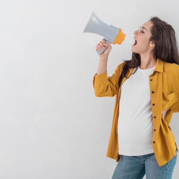 Zijaanzicht van zwangere vrouw die in megafoon schreeuwt Gratis Foto
