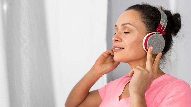Zijaanzicht van zwangere vrouw thuis luisteren naar muziek op de koptelefoon Gratis Foto