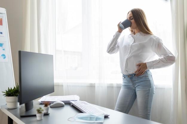 Zijaanzicht van zwangere zakenvrouw met koffie op kantoor Gratis Foto