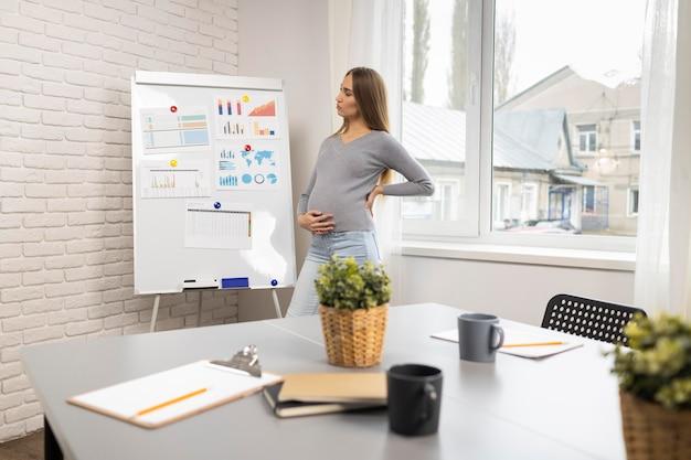 Zijaanzicht van zwangere zakenvrouw met whiteboard in het kantoor Gratis Foto