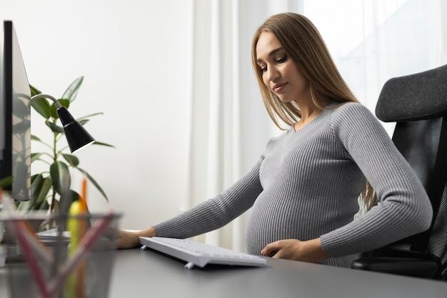 Zijaanzicht van zwangere zakenvrouw op kantoor Gratis Foto