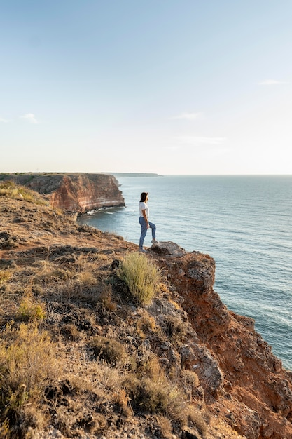 Zijaanzicht vrouw genieten van het uitzicht op een kust Gratis Foto