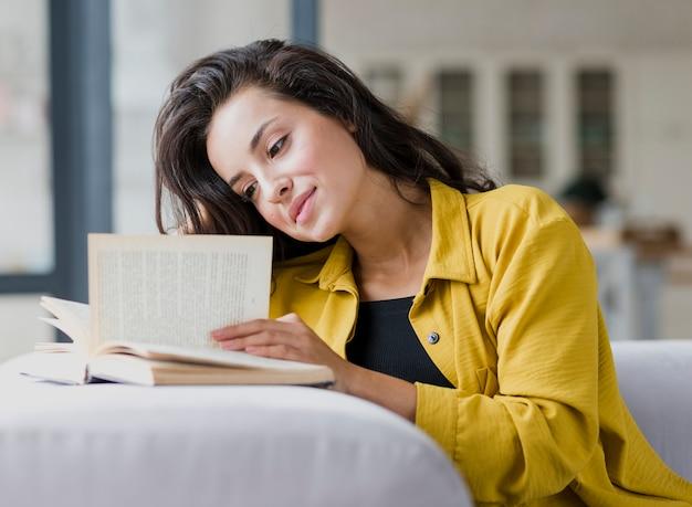 Zijaanzicht vrouw lezing op sofa Gratis Foto
