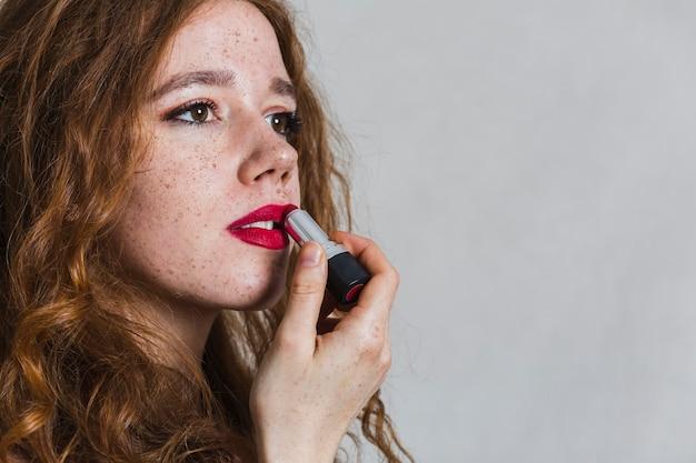 Zijaanzicht vrouw met behulp van een lippenstift Gratis Foto