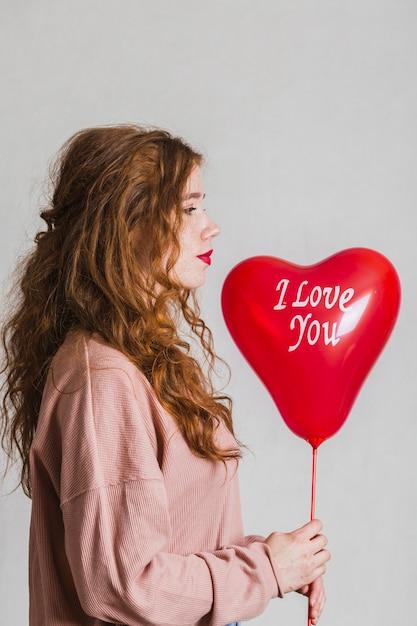 Zijaanzicht vrouw met een valentijn dag ballon Gratis Foto