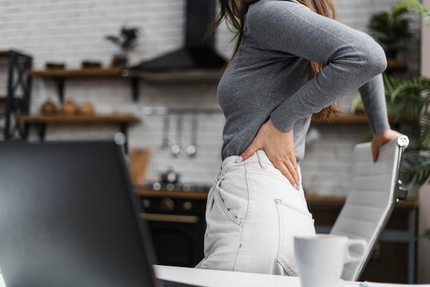 Zijaanzicht vrouw met rugpijn tijdens het werken vanuit huis Gratis Foto