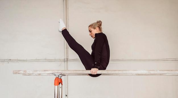 Zijaanzicht vrouw training voor gymnastiek kampioenschap Gratis Foto