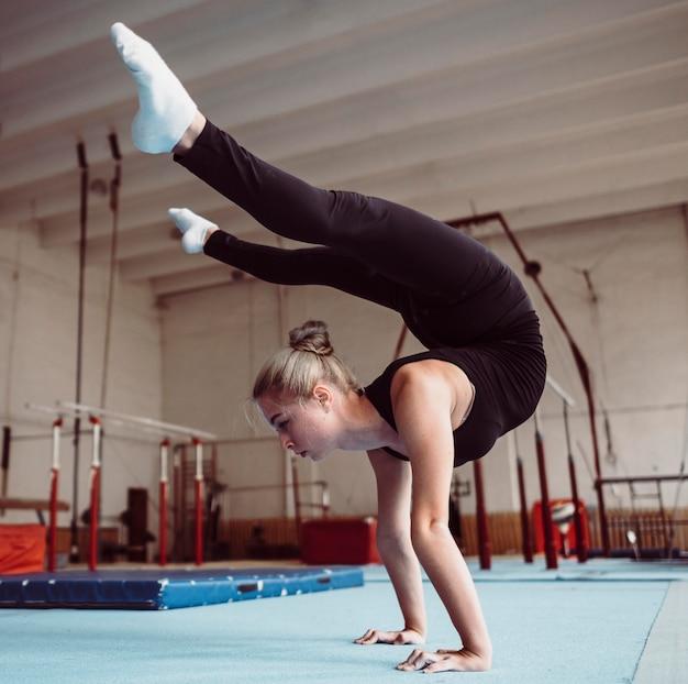 Zijaanzicht vrouw training voor olympische gymnastiek Gratis Foto
