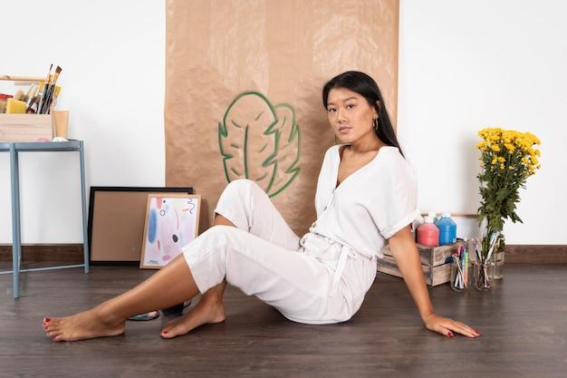 Zijaanzicht vrouw zittend op de vloer Gratis Foto