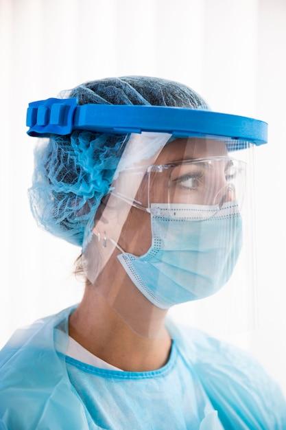Zijaanzicht vrouwelijke arts in beschermende kleding wegkijken Gratis Foto