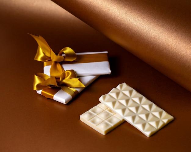 Zijaanzicht witte chocoladerepen met chocolade verpakt in wit papier met gouden linten Gratis Foto