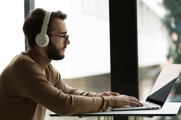 Zijaanzicht zaken man met hoofdtelefoon werken Gratis Foto