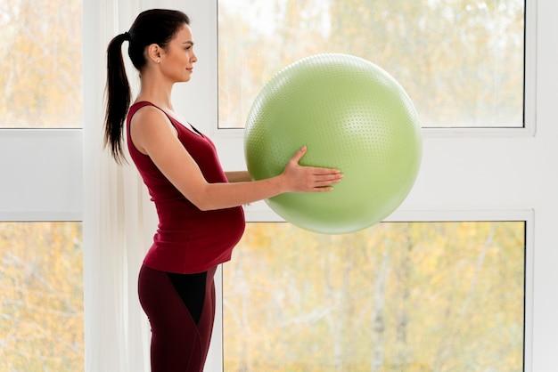 Zijaanzicht zwangere vrouw die een groene geschiktheidsbal houdt Gratis Foto
