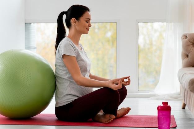 Zijaanzicht zwangere vrouw mediteren met kopie ruimte Gratis Foto