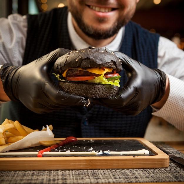 Zijaanzicht zwarte hamburger met wegwerphandschoenen en menselijke hand en frietjes in houten dienblad op restaurant Gratis Foto