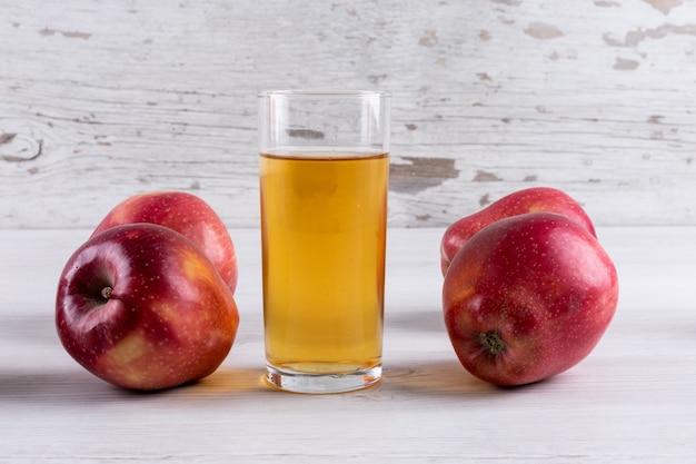 Zijaanzichtappelsap met rode appelen op witte houten lijst Gratis Foto