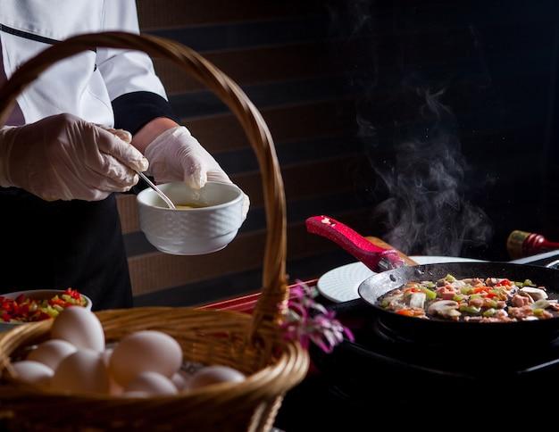 Zijaanzichtchef-kok die heerlijke maaltijd in keuken voorbereiden. Gratis Foto