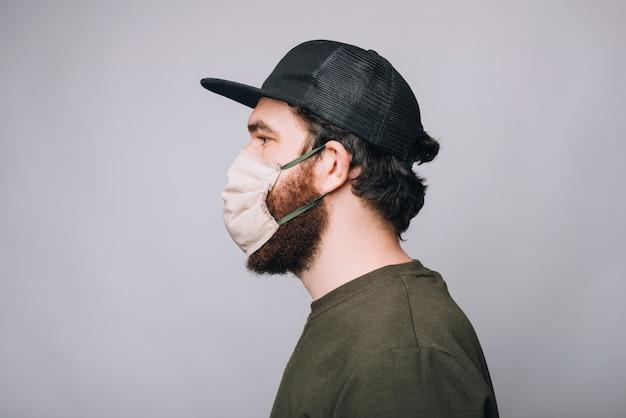 Zijaanzichtfoto van het gebaarde hipster man wering masker voor anti covid bescherming Premium Foto