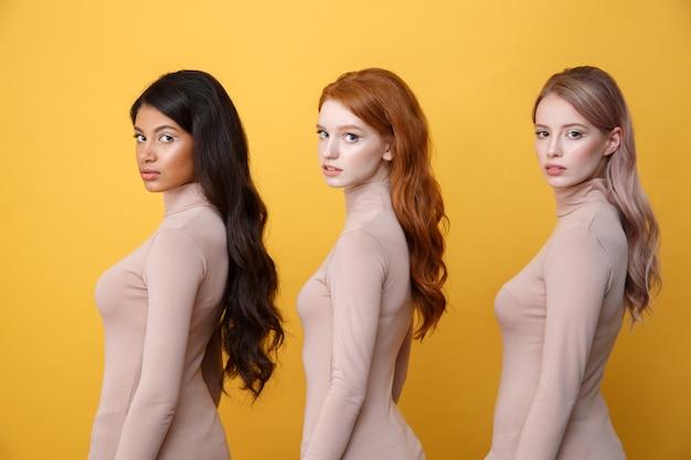 Zijaanzichtfoto van jonge ernstige drie dames Gratis Foto