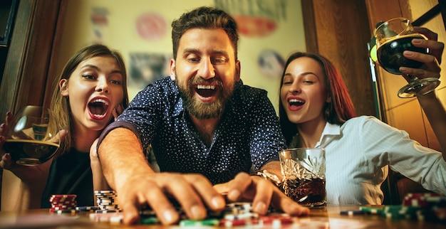 Zijaanzichtfoto van vrienden die bij houten lijst zitten. vrienden plezier tijdens het spelen van bordspel. Gratis Foto
