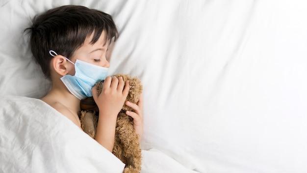 Zijaanzichtjongen met teddybeer in bed Gratis Foto