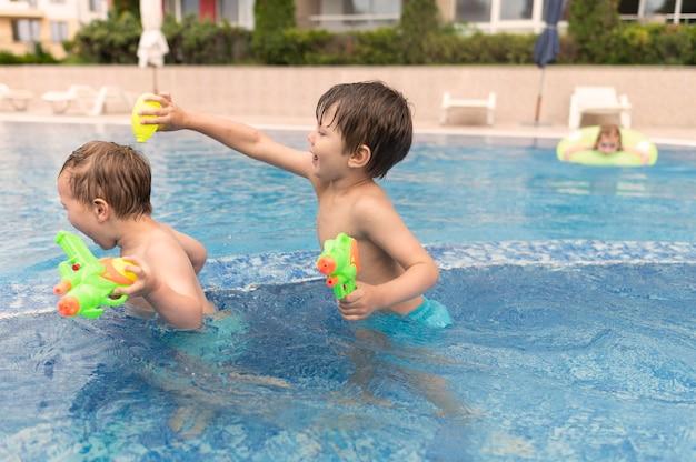 Zijaanzichtjongens die bij pool spelen Gratis Foto