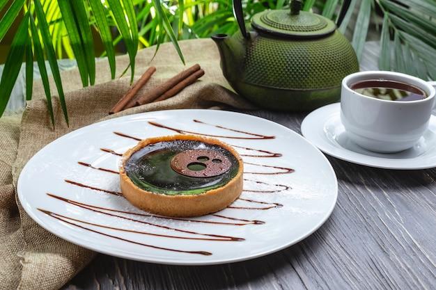 Zijaanzichtkoekjes met gelei en chocoladesuikerglazuur met een kop thee Gratis Foto