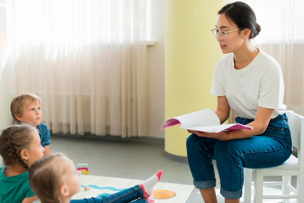 Zijaanzichtleraar leest een verhaal voor haar studenten Gratis Foto