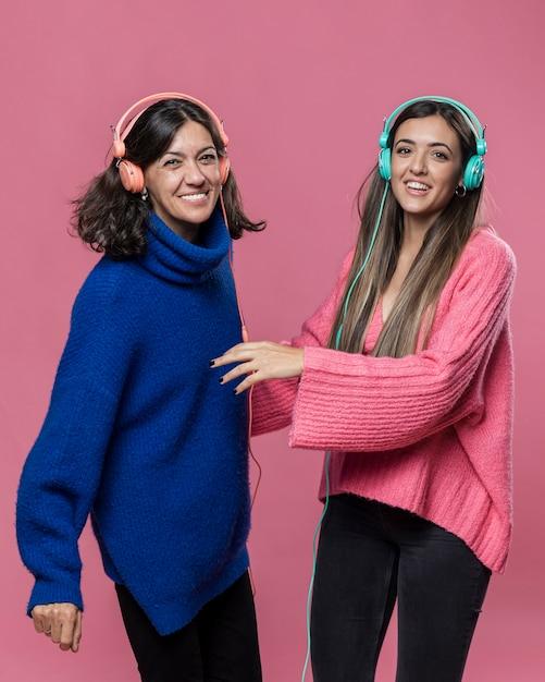 Zijaanzichtmama en dochter het luisteren muziek Gratis Foto