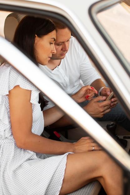 Zijaanzichtman en vrouw met telefoon Gratis Foto