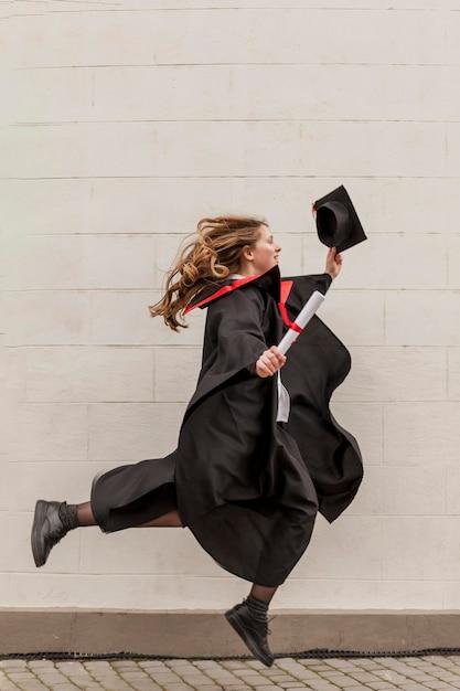 Zijaanzichtmeisje die bij graduatie springen Gratis Foto