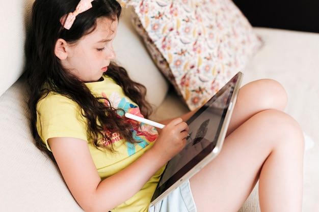 Zijaanzichtmeisje die op een tablet trekken Gratis Foto