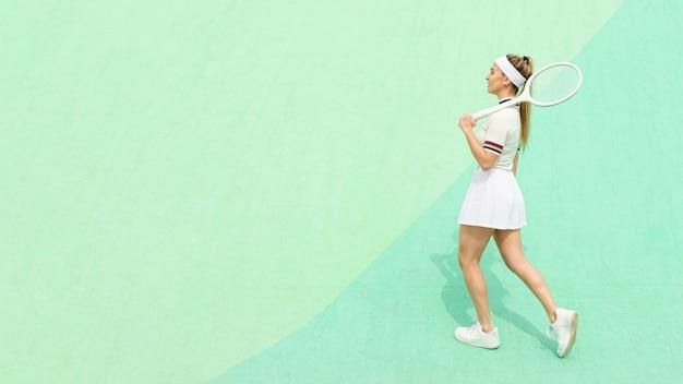 Zijaanzichtmeisje met tennisracket op een tennisgebied Gratis Foto