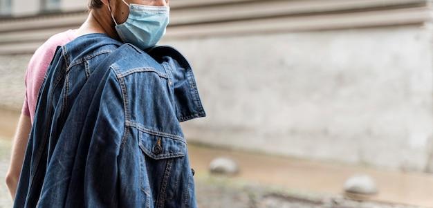 Zijaanzichtmens die een medisch masker buiten met exemplaarruimte draagt Gratis Foto