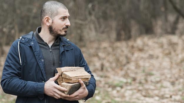 Zijaanzichtmens dragend hout Gratis Foto