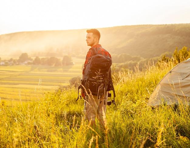Zijaanzichtmens op groen gebied met rugzak Gratis Foto