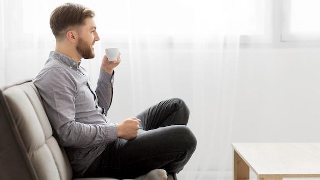 Zijaanzichtmens op laag het drinken koffie Gratis Foto