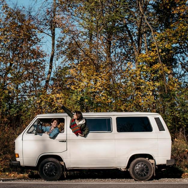 Zijaanzichtmensen die een roadtrip maken in een wit busje Gratis Foto