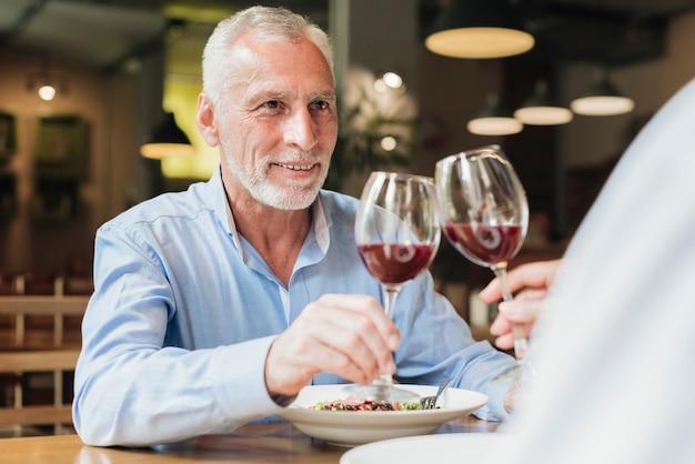 Zijaanzichtmensen die glazen rammelen bij restaurant Gratis Foto