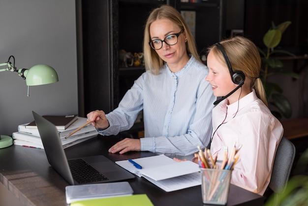 Zijaanzichtmoeder en dochter die bij een online klasse deelnemen Gratis Foto