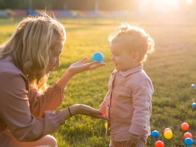 Zijaanzichtmoeder en kind het spelen met plastic ballen Gratis Foto