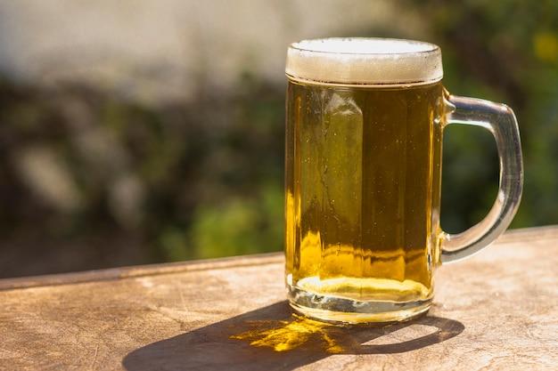 Zijaanzichtpint met schuimend bier op lijst Premium Foto