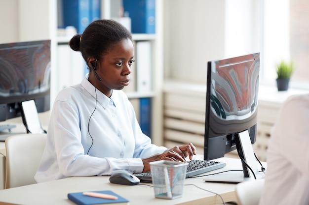 Zijaanzichtportret van afrikaans-amerikaanse vrouw die hoofdtelefoon draagt en laptop gebruikt tijdens het werken aan klantenservice Premium Foto
