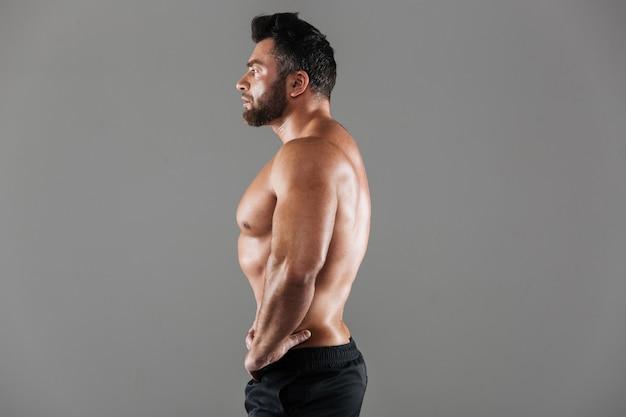 Zijaanzichtportret van een geconcentreerde sterke shirtless mannelijke bodybuilder Gratis Foto