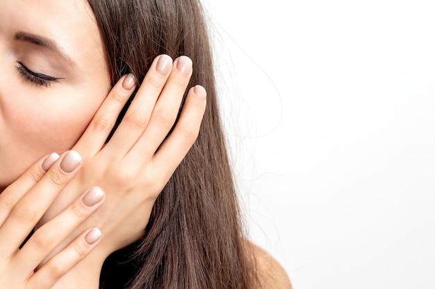 Zijaanzichtportret van mooie jonge kaukasische donkerbruine vrouw met gesloten ogen die haar haar aanraken door gemanicuurde vingers op witte muur Premium Foto