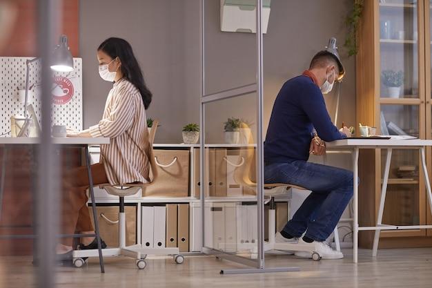 Zijaanzichtportret van twee mensen die maskers in bureau dragen terwijl zij aan bureaus in afzonderlijke hokjes werken na pandemie, exemplaarruimte Premium Foto
